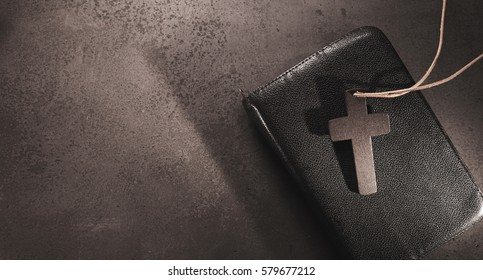 Worthy Grief card on stone background. Funeral invitation with prayer book and crucifix on concrete background