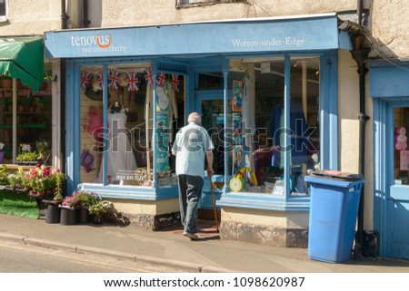 Wotton-under-Edge, England - May 10, 2018: Tenovus Charity Shop on Long Street, eldery person with a walking stick