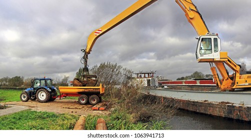 Woubrugge, Netherlands - November 7, 2012: a ship-mounted crane deposits clay from a large barge into a trailer pulled by a tracktor. Part of dike reenforcement work in a polder.  Dark and cloudy sky.