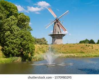 WOUDRICHEM, NETHERLANDS - JUN 4, 2017: Moat, rampart and corn mill Nooit Gedagt in old fortified town of Woudrichem, Brabant, Netherlands