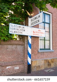 WOUDRICHEM, NETHERLANDS - JUN 4, 2017: Nostalgic ANWB signpost or road sign in old town of fortified city Woudrichem, Noord-Brabant, Netherlands
