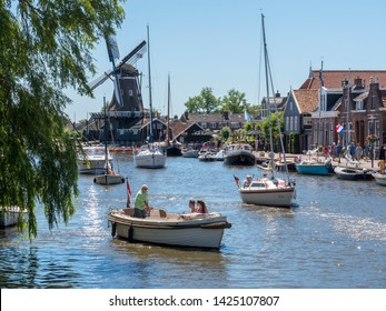 Woudsend, The Netherlands - June 30 2018: On a summer day, many water sports enthusiasts pass the tourist-oriented village in Friesland with their sloop, sailing boat or motorboat.