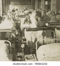 Wounded American soldiers in the New York City Convalescent Hospital No. 5. during World War 1. Nurses attend recovering men in a packed ward in 1917-1918
