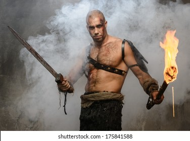 Wounded gladiator holding torch and sword covered in blood