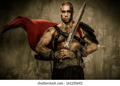 Wounded gladiator in waving coat holding sword covered in blood