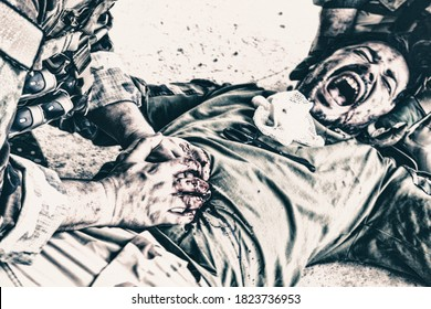 Wounded soldier, commando fighter lying on floor, screaming in pain while comrade pressing with hands on wound in his stomach, trying stop bleeding and save life. Tactical casualty care on battlefield