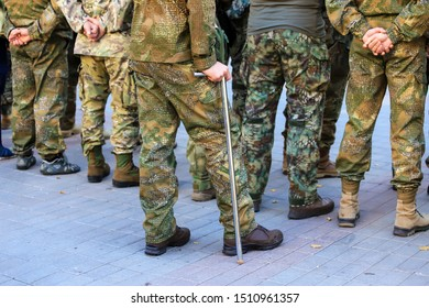 A wounded soldier of the Ukrainian army stands with a crutch near the formation of war veterans,  Defender of Ukraine Day. Armed forces of Ukraine, Ukrainian war