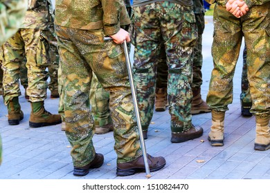 A wounded soldier of the Ukrainian army in uniform stands with a crutch near the formation of war veterans at the celebration of Defender Ukraine Day. Armed forces of Ukraine, Ukrainian war