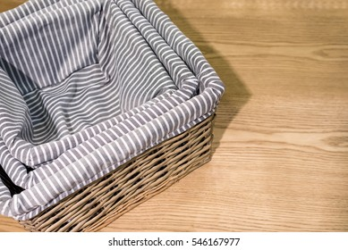 woven bamboo basket covered with grey and white stripe cloth