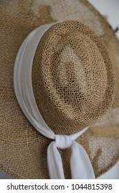 A woven country sun hat with a long white ribbon hanging on a wall  next to the door. Easy to grab on the way out fro protection  on a  sunny day.