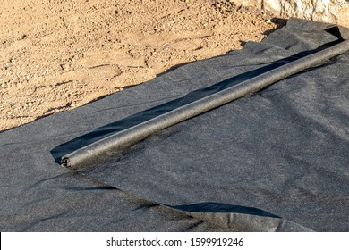 Woven geotextile fabric rolling out on the ground in the summer garden under reconstruction