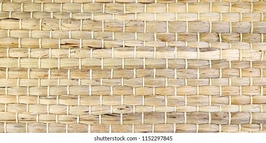 A woven Mat of reeds or straw-yellow in color. The texture of dry cane. Light yellow.