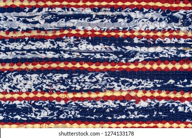 Woven rug fabric on the background. Cloth, typically produced by weaving or knitting textile fibers. Close up
