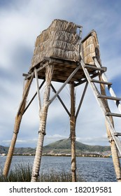A woven watch tower made of reeds at Lake Titicaca on a sunny day.