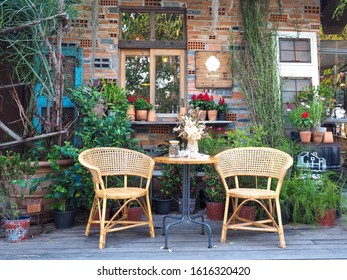 Woven wooden chairs and side table, wall decorated with various trees