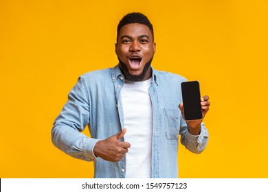 Wow, amazing app. Surprised african man holding smartphone with black screen and showing thumb up, yellow background with free space