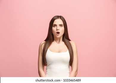 Wow. Beautiful female half-length front portrait isolated on pink studio backgroud. Young emotional surprised woman standing with open mouth. Human emotions, facial expression concept. Trendy colors