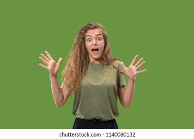 Wow. Beautiful female half-length front portrait isolated on green studio backgroud. Young emotional surprised woman standing with open mouth. Human emotions, facial expression concept. Trendy colors