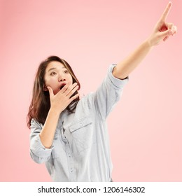 Wow. Beautiful female half-length front portrait isolated on pink studio backgroud. Young emotional surprised woman standing and pointing up. Human emotions, facial expression concept. Trendy colors