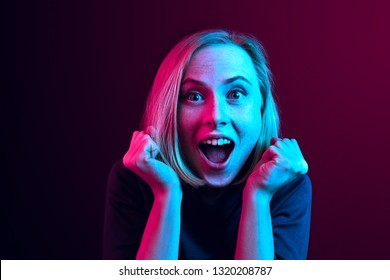 Wow. Beautiful female half-length front portrait isolated on neon studio backgroud. Young emotional surprised woman standing with open mouth. Human emotions, facial expression concept. Trendy colors