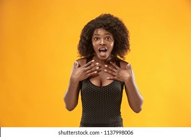 Wow. Beautiful female half-length portrait isolated on gold studio backgroud. Young surprised woman holding hands by head, looking at camera. Human emotions, facial expression concept. Trendy colors