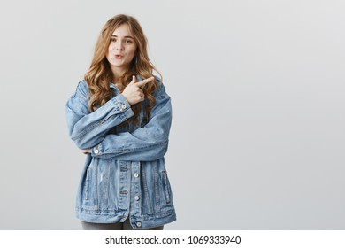 Wow, check this out, I am intrigued. Studio portrait of interested good-looking female travel blogger in stylish denim jacket, folding lips from desire and interest, pointing at upper right corner