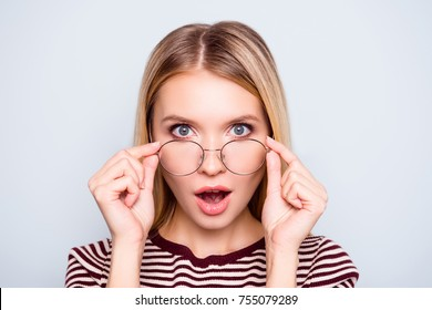 Wow! I don't believe you! Close up portrait of shocked astonished woman with open mouth and big eyes, she is touching her spectacles