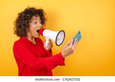 Wow!! excited Young arab woman wearing red shirt holding a megaphone over yellow background  shouting with megaphone a mobile phone