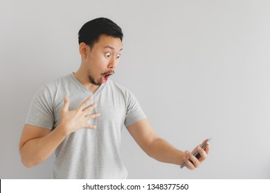 Wow face of Asian man in grey t-shirt get surprised on the smartphone.