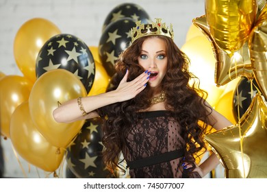 Wow face. Shocked woman with expressive facial expressions volume hair. Surprised girl in crown princess with updo hair presenting your product among the golden balloons, party