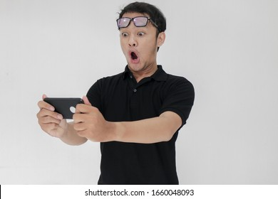 Wow face of Your Asian man shocked what he see in the smartphone on isolated grey background. Indonesia Man wear black shirt Isolated grey background.