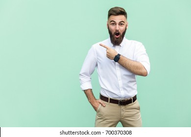 Wow! Handsome young adult man with beard in shocked. Pointing away while standing isolated on light green background