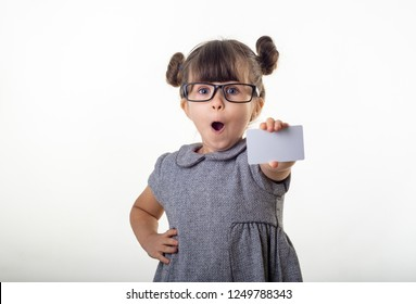 Wow! Happy shocked child holding discount white card in her hands. Surprised kid with credit card. Little girl with glasses showing empty blank paper note copy space.