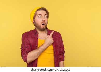 Wow, look, advertise here! Surprised hipster guy pointing aside and looking at copy space with shocked amazed expression, showing blank yellow background for crazy commercial idea. indoor isolated
