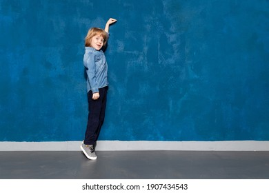 Wow look, empty place on wall for advertising. Amazed kid boy on tiptoe pointing to blank space on background. Surprised preschooler showing height on backdrop with copyspace for ad.