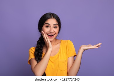 Wow, Look Here. Portarit of smiling young indian lady holding outstretched hand with open palm, advertising and showing free empty space and touching her cheek posing isolated on purple studio wall