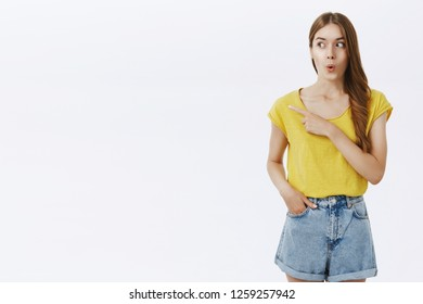 Wow looks cool. Amused and excited attractive caucasian female in yellow t-shirt folding lips from amazement and surprise gazing and pointing left with curious and interested look over white wall