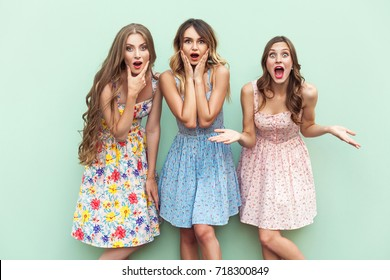 Wow! No way ! Sexy long haired girls in dress, looking at camera with surprised face . Green background, studio shot