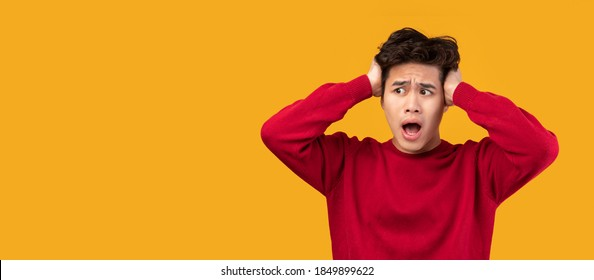 Wow, No Way, It's Unbelievable. Portrait of surprised asian guy seeing shocking advertisement, emotionally reacting with open mouth, grabbing his head and looking away at copy space, panorama, banner