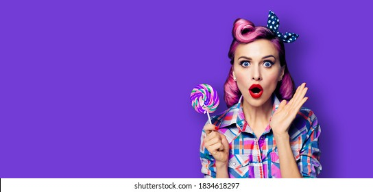 Wow! Purple head excited very surprised woman with lollipop. Pinup girl with wide opened mouth, eyes. Beauty model at retro fashion and vintage concept. Violet color background with copyspace for text