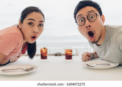 Wow and Shocked face of Asian lover couple having a date at the restaurant on the beach.