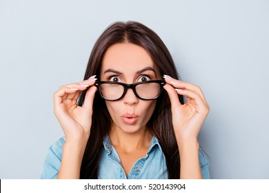 Wow! Shocked pretty woman touching her glasses.