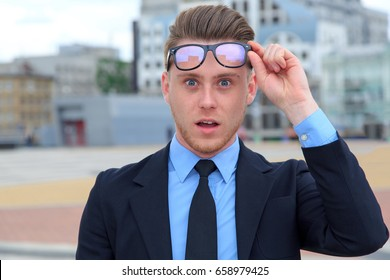 Wow! Shocked young man in glasses with open mouth. Surprised young business man touching glasses.