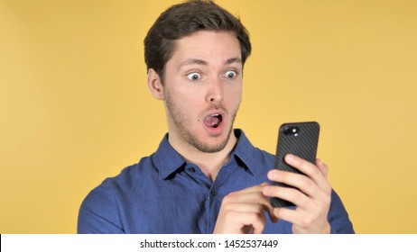 Wow, Surprised Casual Young Man Using Smartphone on Yellow Background
