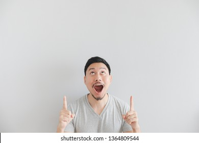 Wow and surprised face of Asian man in grey t-shirt with hand point on empty space.