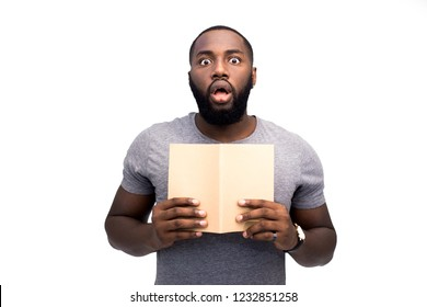 Wow! Is it true? Surprised face of black African American teacher. He reading notebook of his learner and having shock effect. Shock content. Education concept. Isolated on white studio background