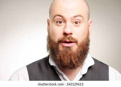 Wow! Surprised young caucasian bearded man in white shirt staring at camera while standing against gray background