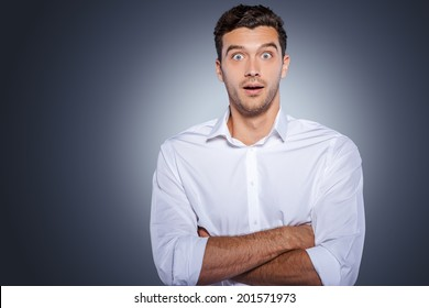 Wow! Surprised young man in white shirt staring at camera and keeping arms crossed while standing against grey background