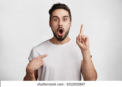 Wow, I understand it! Surprised bearded young male keeps mouth widely opened, points at himself, raises fore finger as remembers something, isolated over white background. Reaction and people