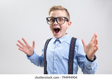 Wow. Waist up portrait of shocked child opening his mouth with pleasant surprise. He is looking at camera and spreading his hands. Isolated on background